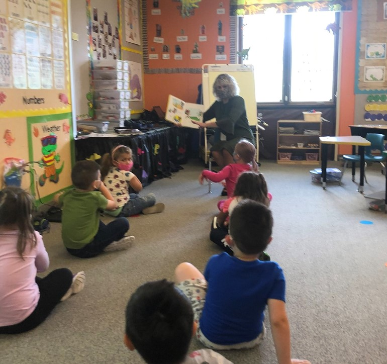Dr. Tomcho reading a book to students in K4
